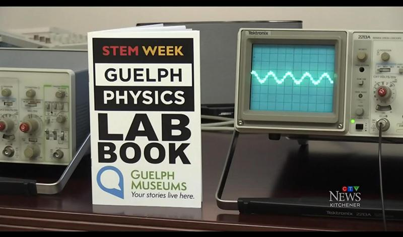 Physics Lab Book, with science equipment in the background