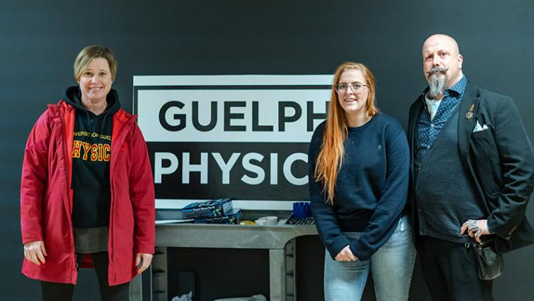 Joanne O'Meara, Samantha Buck and the Great Orbax posing in front of the Guelph Physics sign