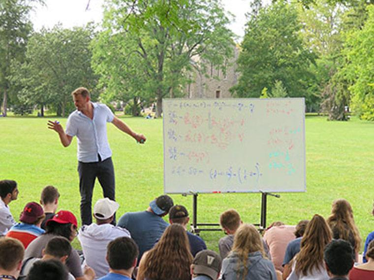 man lecturing to a large group of students outside sitting on the grass