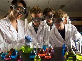 Students in the lab wearing safety glasses and lab coats doing an experiment with beakers filled with colored liquids