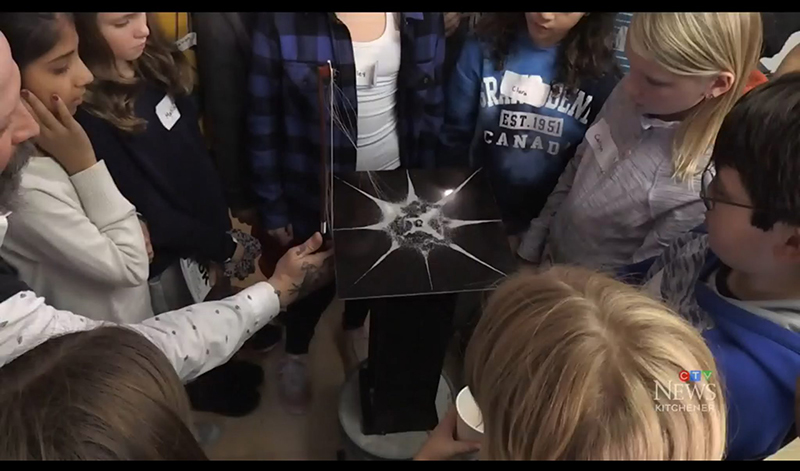 Children gathered in circle watching physics demonstration