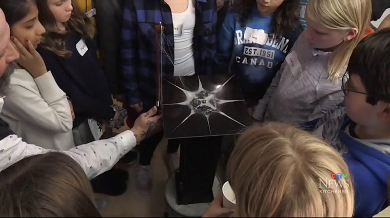 Students gathered around a pedestal for a demonstration of vibration frequency