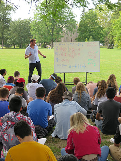 Dr. Dennis Muecher teaching outside to a group of students sitting on Johnston Green
