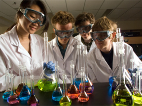 group of four students in the lab wearing googles and looking at beakers of different coloured liquids