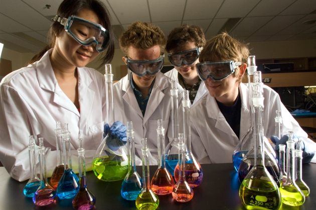 Four students with goggles and lab coats looking at colourful liquids in lab glassware