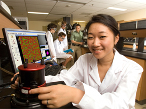 student using microscope and computer view sample
