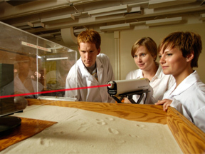three people in the lab using a laser