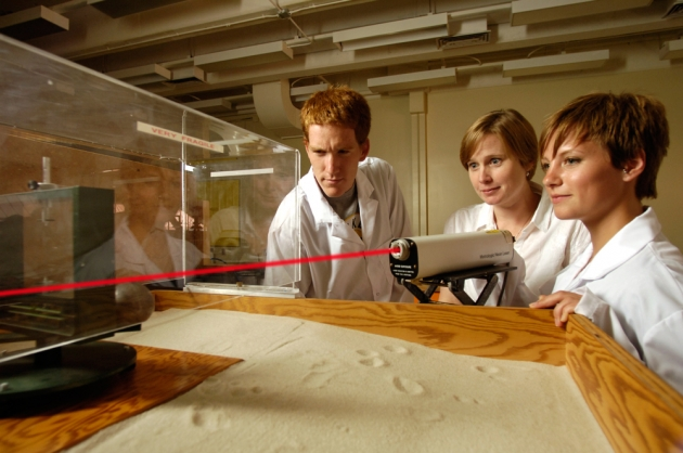 Three people in the lab running an experiment with a laser