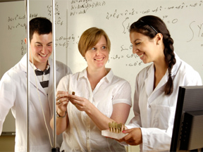 three people standing in classroom working with equipment, equations on the board behind them