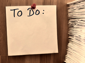 to do list tacked to wall beside a stack of papers